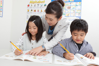 AEON teacher demonstrating student care by checking the students' homework
