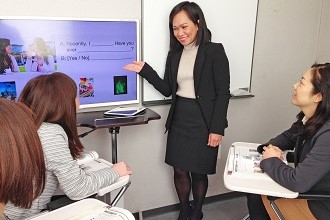 AEON teacher teaching lessons for adults Three students are listening attentively while the teacher is going over the grammar target